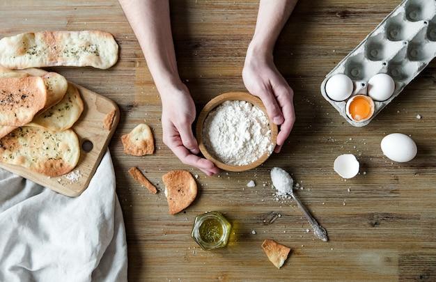Focaccia italiana sottile con spezie. tortillas sottili, focaccia italiana tradizionale con olio d'oliva e sale. processo di cottura con ingredienti con le mani.