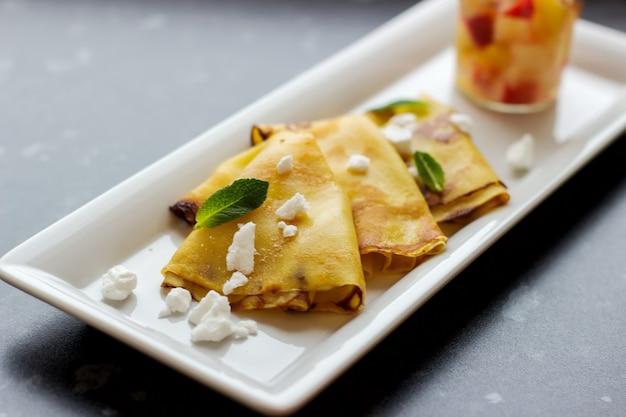 Pancake sottili all'arancia, fette di formaggio con foglia di menta su piatto bianco sul tavolo