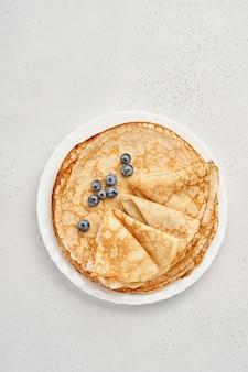 Frittelle sottili, crepes o blini con frutti di bosco in un piatto bianco. vista dall'alto. settimana del pancake. shrovetide. spazio per il testo.