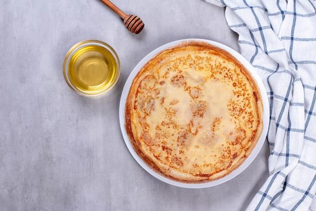 Frittelle sottili su un piatto bianco con miele. vista dall'alto.