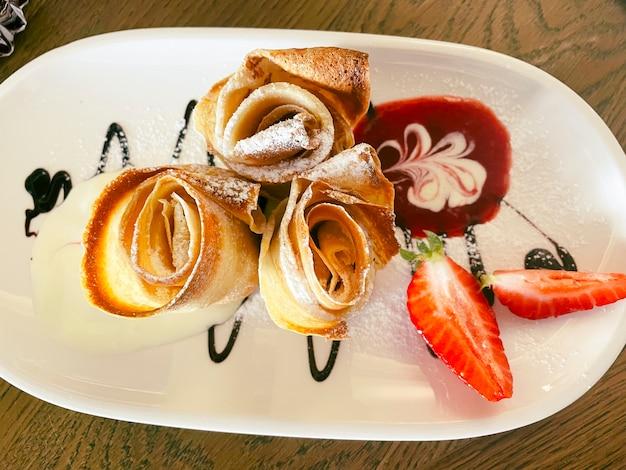 Pancake sottili con fragole fresche e menta. foto di cibo
