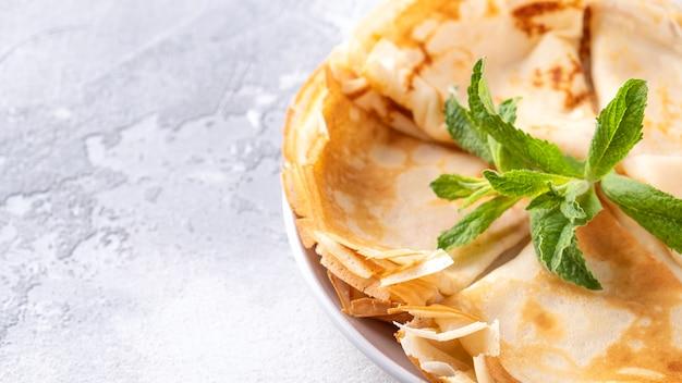 Frittelle sottili con menta su un piatto.