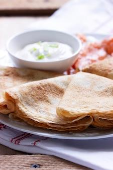 Frittelle sottili con salmone e panna acida su uno sfondo chiaro. stile rustico, messa a fuoco selettiva.