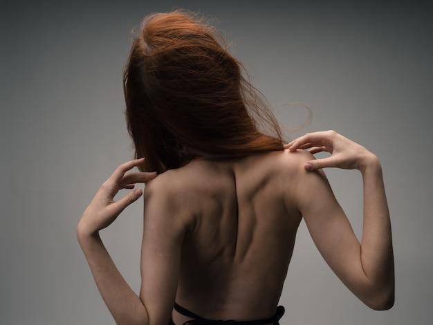 Una donna magra dai capelli rossi si tocca con le mani dietro la schiena.