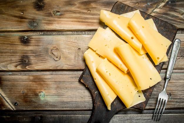 Fette sottili di formaggio sul tagliere. su uno sfondo di legno.
