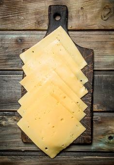 Fette sottili di formaggio sul tagliere. su una superficie di legno.