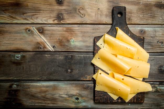 Fette sottili di formaggio sul tagliere sulla tavola di legno.