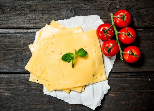 Fette sottili di formaggio con pomodorini e un rametto di menta. su una superficie di legno.