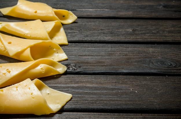 Fette sottili di formaggio. su una superficie di legno.