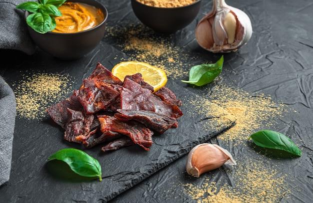 Fette sottili di carne secca su una parete nera lucida con spezie, basilico e aglio. vista laterale con copia spazio.