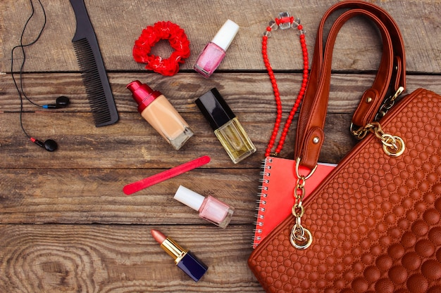 Cose da borsetta aperta della signora. borsa delle donne su fondo di legno. immagine tonica.
