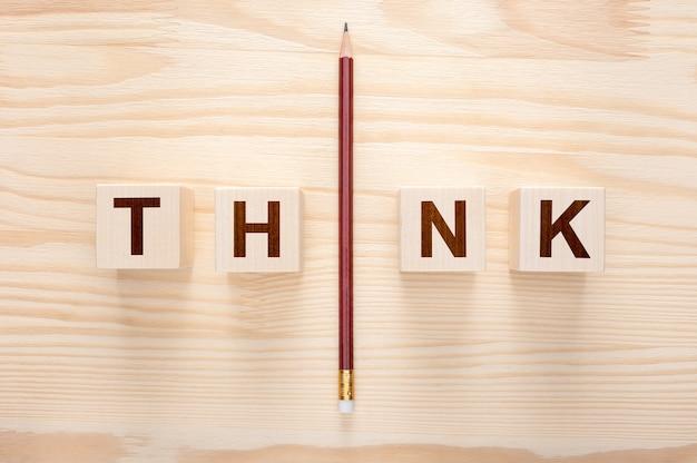 Pensa al concetto. parola pensare su sfondo di legno. una matita con la parola pensa.