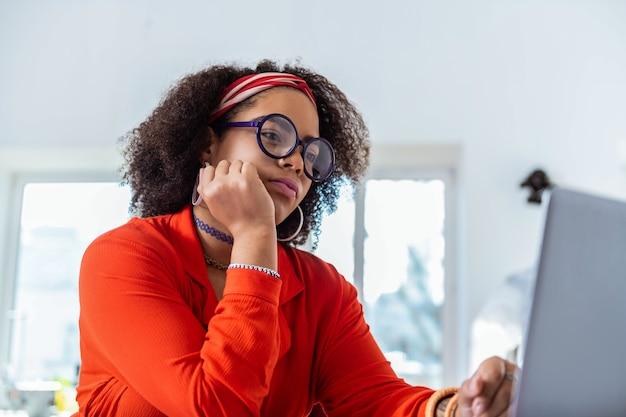 Pensando al carico di lavoro. signora attraente concentrata che pensa attivamente al suo lavoro e ne pianifica l'inizio
