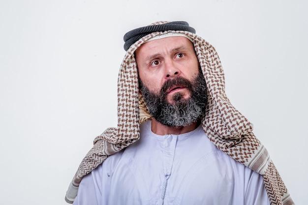 Uomo arabo di pensiero in posa su sfondo bianco.