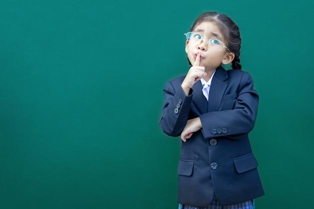 Pensando i bambini della scuola asiatica con uniforme formale di affari su sfondo verde