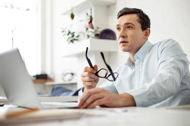 Pensiero. uomo dai capelli scuri concentrato attraente che lavora al suo laptop e che tiene gli occhiali mentre era seduto al tavolo