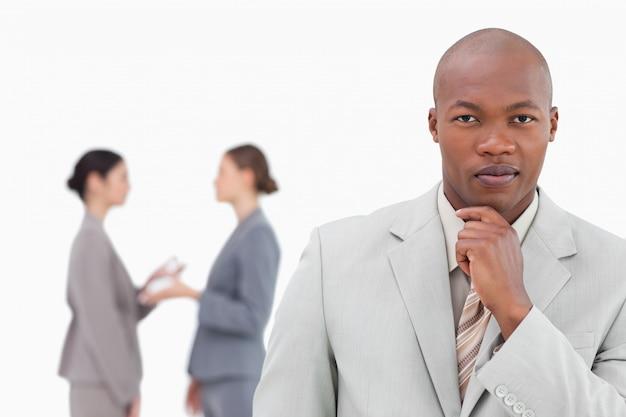 Uomo d'affari di pensiero con i colleghi dietro di lui