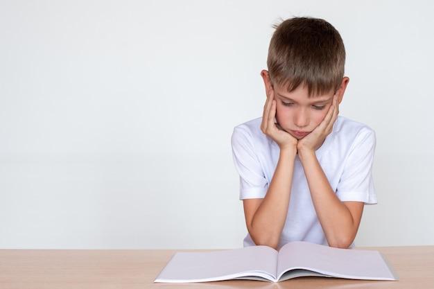 Ragazzo bambino di pensiero che osserva in un taccuino o in un libro, seduto al tavolo e facendo i compiti