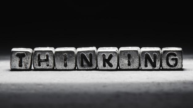 Lettering concetto di pensiero su cubi di metallo isolato su priorità bassa nera