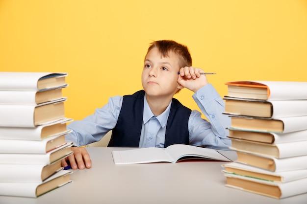 Pensando allievo ragazzo carino nel proseguo dello studio con molti libri.