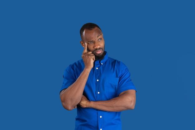 Pensare, sognare. ritratto monocromatico di giovane uomo afroamericano isolato sulla parete blu. bellissimo modello maschile. emozioni umane, espressione facciale, vendite, concetto di annuncio. cultura giovanile.