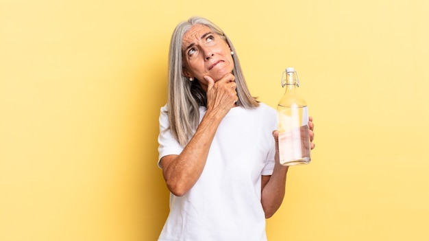 Pensare, sentirsi dubbiosi e confusi, con diverse opzioni, chiedendosi quale decisione prendere e tenendo in mano una bottiglia d'acqua