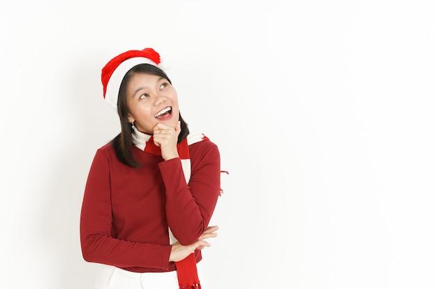 Gesto pensante di bella donna asiatica che indossa dolcevita rosso e cappello da babbo natale isolato su bianco