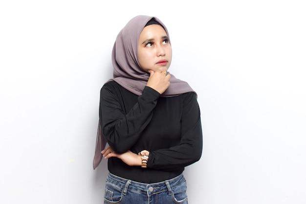 Gesto di pensiero di giovani belle donne asiatiche musulmane vestono velo hijab e camicia nera