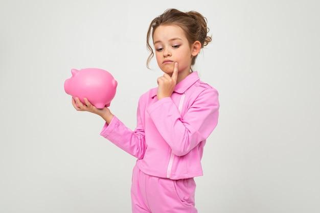 Ragazza di pensiero in un abito rosa in possesso di un barattolo di denaro su un muro bianco con uno spazio vuoto