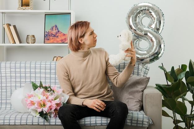 Pensando a un bel ragazzo durante la giornata delle donne felici che tiene e guarda l'orsacchiotto seduto sul divano nel soggiorno