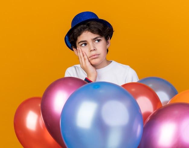 Pensando che guarda di lato un ragazzino che indossa un cappello da festa blu in piedi dietro i palloncini mettendo la mano sulla guancia isolata sul muro arancione
