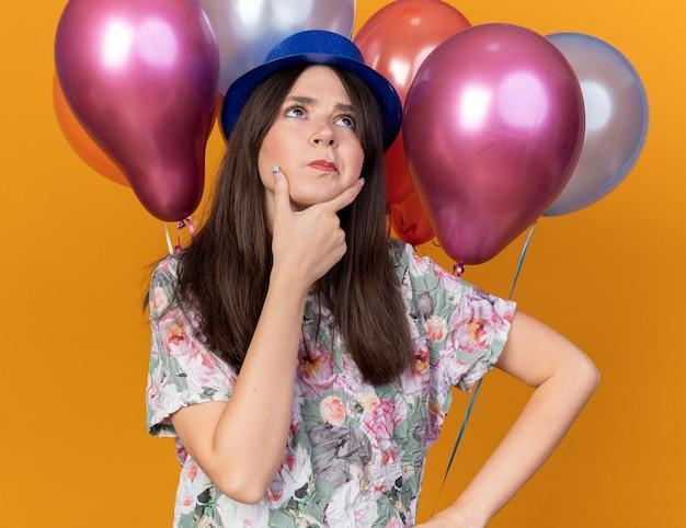 Pensando di guardare in alto la giovane bella donna che indossa un cappello da festa in piedi davanti ai palloncini ha afferrato il mento isolato sul muro arancione
