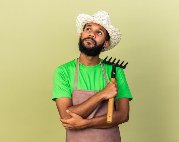 Pensando di guardare il giovane giardiniere afro-americano che indossa un cappello da giardinaggio che tiene il rastrello isolato sul muro verde oliva