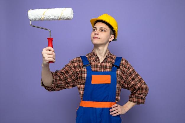 Pensando di mettere la mano sull'anca giovane costruttore maschio che indossa l'uniforme tenendo e guardando la spazzola a rullo