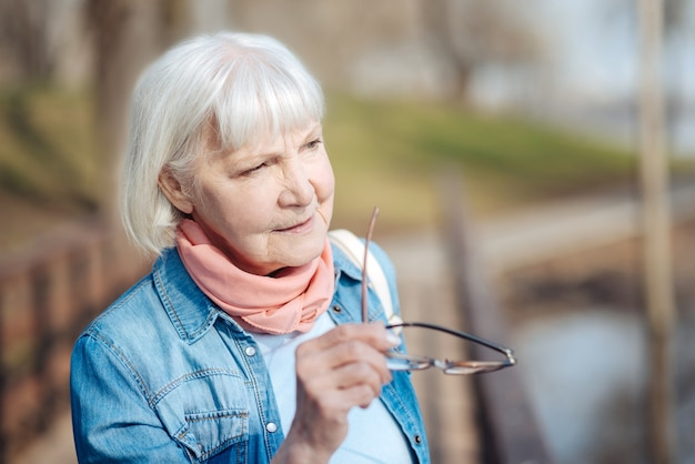 Pensiero. premurosa donna matura tenendo gli occhiali e guardando in lontananza