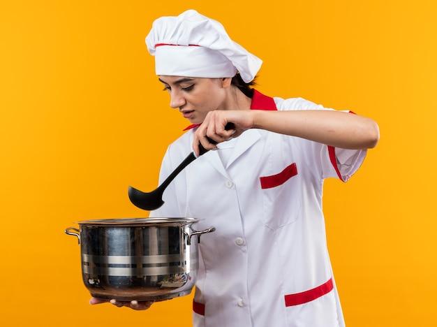 Pensando a una giovane bella ragazza in uniforme da chef che tiene e guarda la casseruola