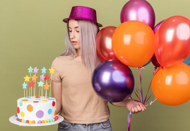 Pensando giovane bella ragazza con palloncini guardando la torta in mano isolata sulla parete verde oliva