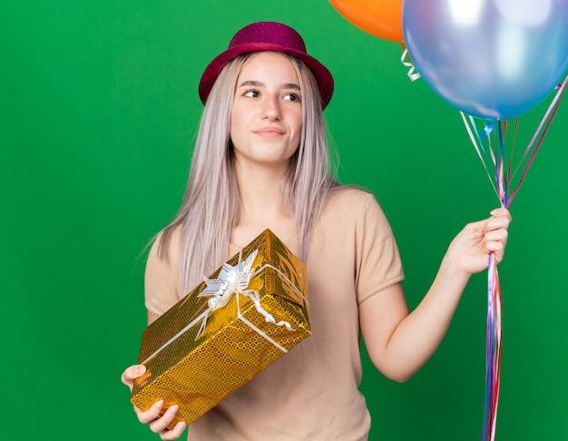 Pensando giovane bella ragazza che indossa cappello da festa e bretelle che tengono palloncini che tengono una scatola regalo isolata sul muro verde
