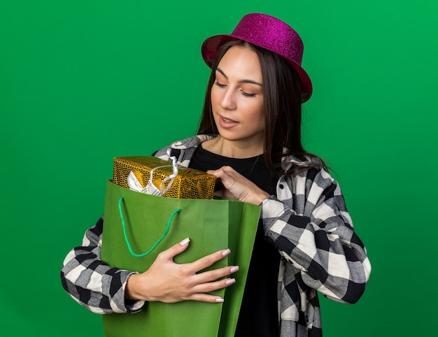 Pensando giovane bella donna che indossa cappello da festa tenendo e guardando la borsa regalo isolata sul muro verde