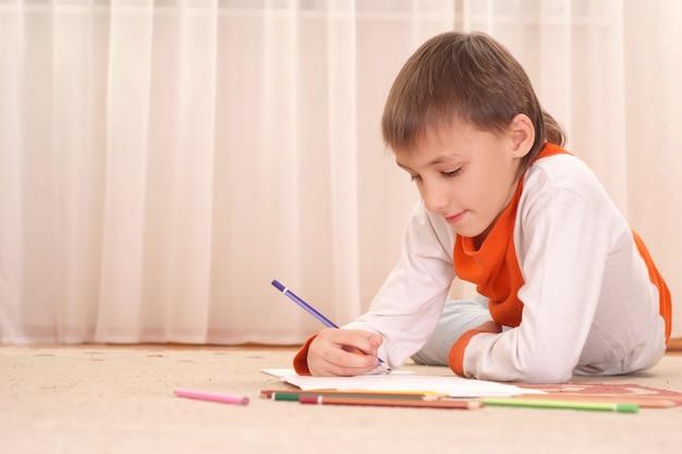 Pensare ragazzo sul pavimento con le matite