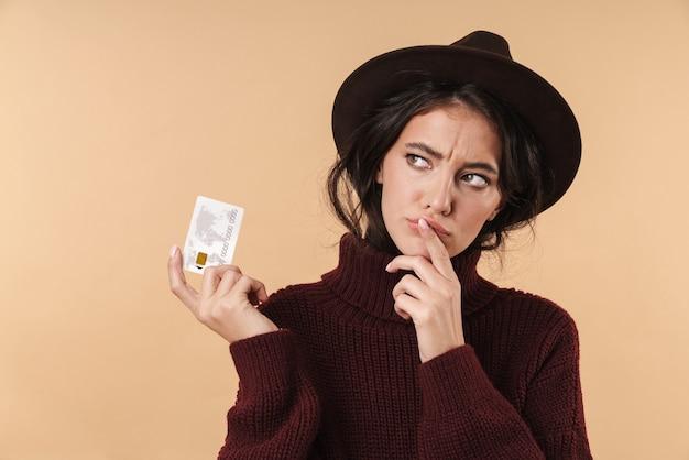 Pensando giovane donna bruna in posa isolato su muro beige muro in possesso di carta di credito.