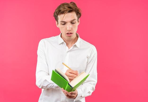 Pensando a un bel ragazzo che indossa una camicia bianca che scrive qualcosa sul libro con una penna isolata sul muro rosa