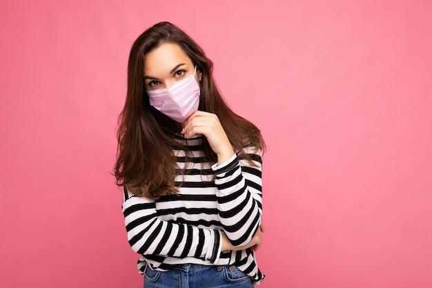 Pensando giovane bella persona di sesso femminile che indossa una maschera facciale mediatica isolata su una parete di fondo rosa. spazio libero