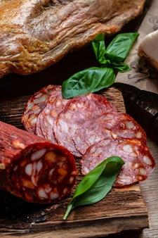 Salame affettato sottilmente con basilico su un fondo di legno. antipasto di carne. immagine verticale. vista dall'alto