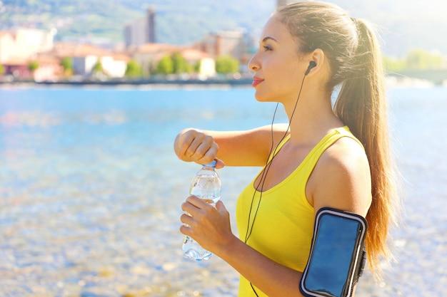 La donna assetata di forma fisica apre una bottiglia d'acqua dopo l'allenamento all'aperto. montare la donna utilizzando l'app fitness per smartphone sulla fascia da braccio per ascoltare musica o come tracker di attività.
