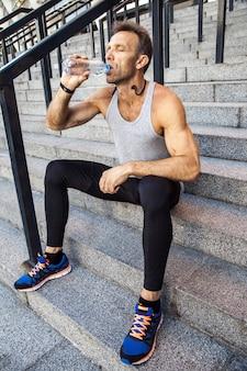 Sportivo assetato riposarsi e bere acqua dopo la corsa. fitness, sport, esercizio e concetto di stile di vita sano delle persone.