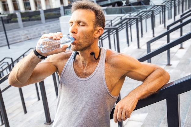 Sportivo assetato riposarsi e bere acqua dopo la corsa