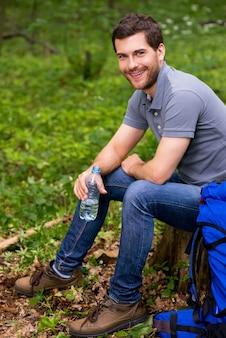 Viaggiatore assetato. bel giovane che tiene in mano una bottiglia con acqua mentre è seduto su un ceppo in una foresta con uno zaino che giace vicino a lui con