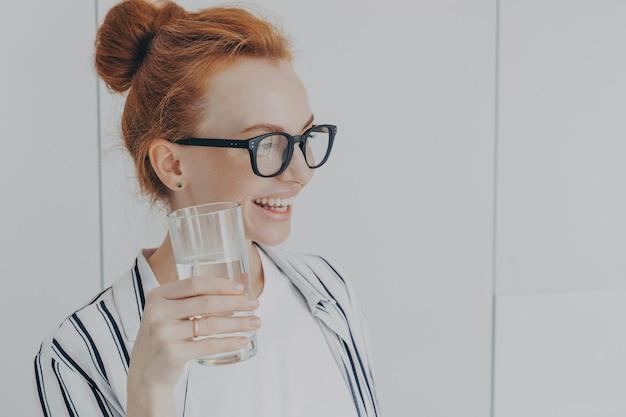 Una donna assetata con i capelli rossi pettinati nel panino beve acqua naturale previene la disidratazione trattiene il vetro