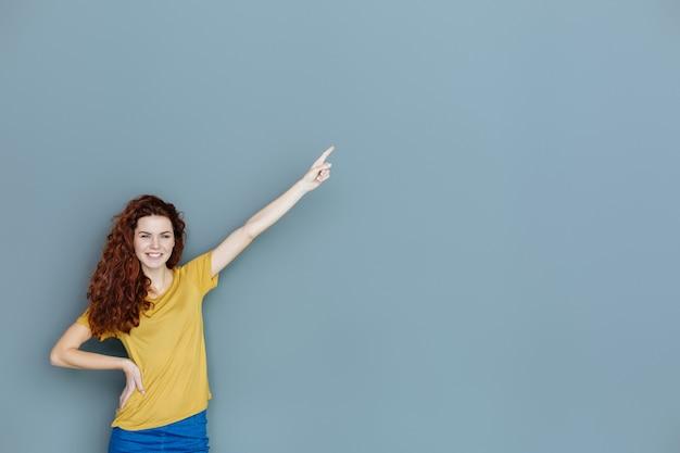 Questa direzione. felice bella donna felice sorridente e indicando con la mano mentre ti guarda